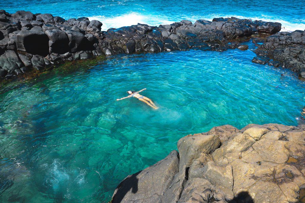 Woman floating in the queens bath natural pool. Kauai hawaii