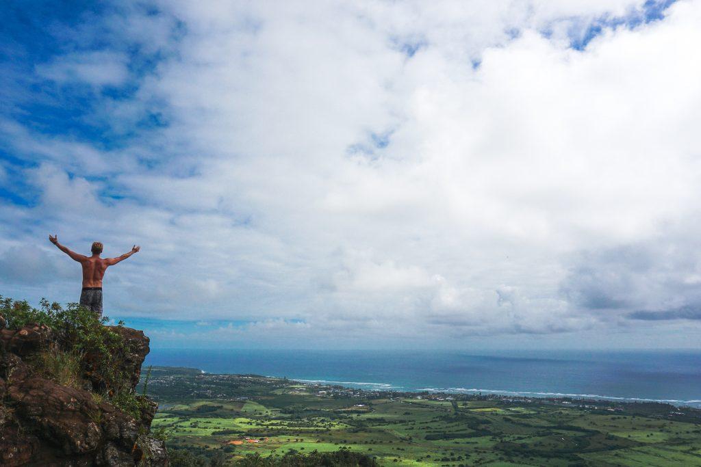 Man on top of sleeping giant mountain kauai hawaii overlooking the island and ocean