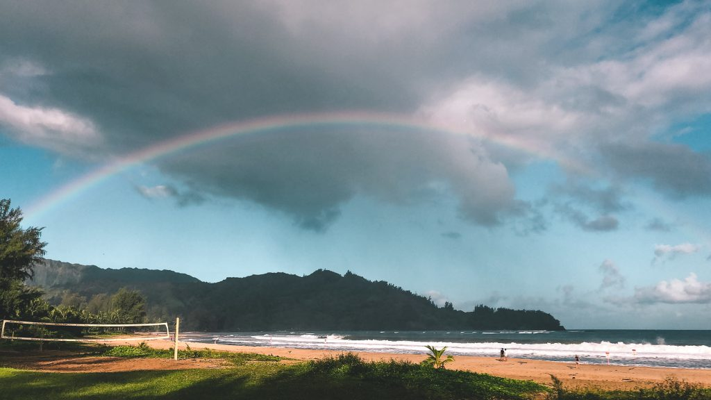 Hanalei Bay Beach with a full rainbow over the mountains.